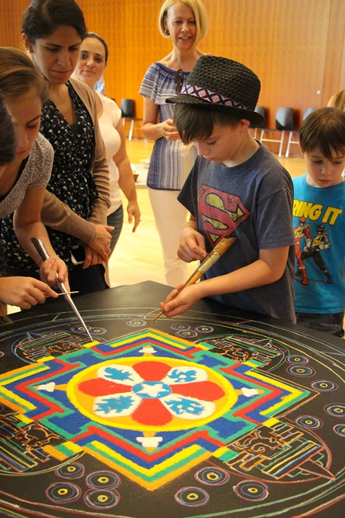A group participates in creating a community mandala. (Jessica Ngo)