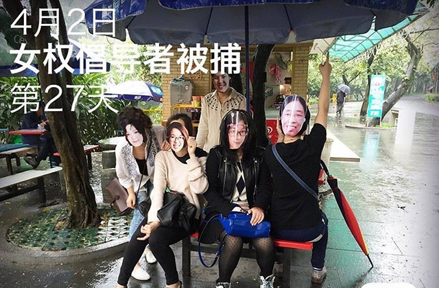 Masked activists pose at an outdoor dining area.
