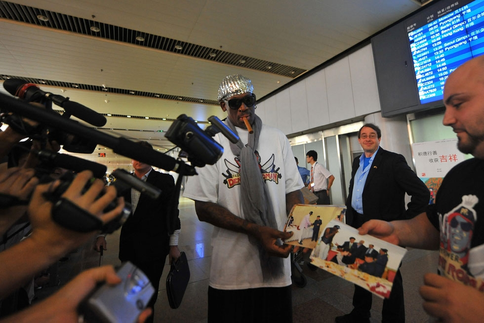 NBA Hall-of-Famer Dennis Rodman shows the press photos from his five-day trip to North Korea, including meetings with Kim Jong Un, as he arrives at Beijing International Airport from Pyongyang on September 7, 2013. (Wang Zhao/AFP/Getty Images)