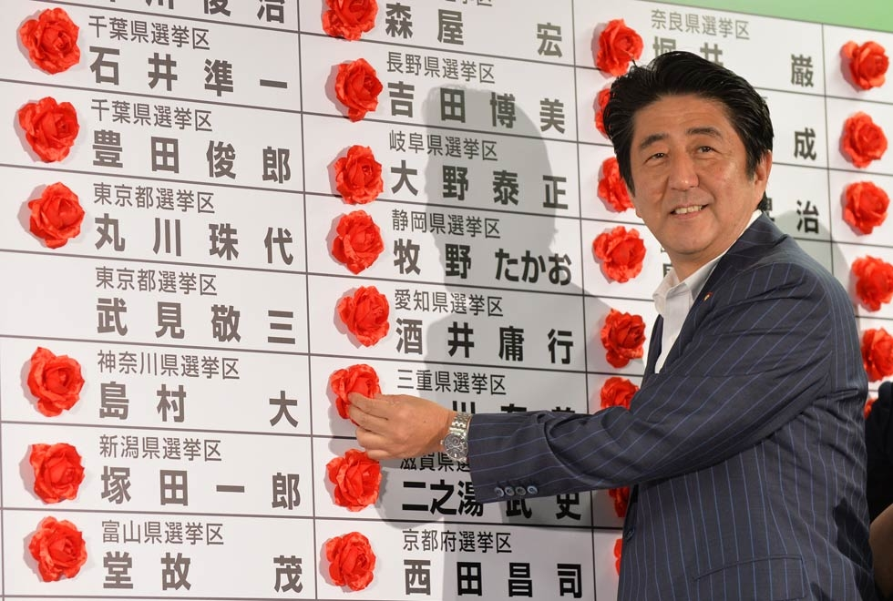 "Japanese Prime Minister and President of the Liberal Democratic Party (LDP) Shinzo Abe claims a decisive victory on July 21, 2013. His economic policies, dubbed ""Abenomics,"" made headlines as Japan's unemployment lowered in 2013. (Kazuhiro Nogi/AFP/Getty Images)"