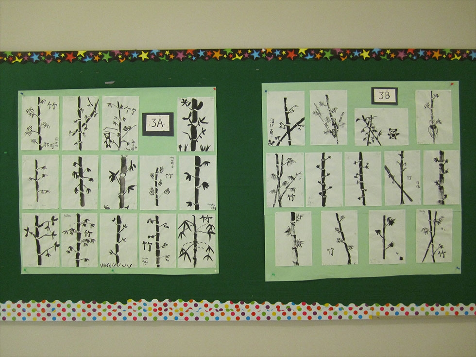 Brush paintings of bamboo by 3rd graders hanging in the hallway.
