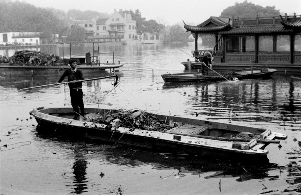 A man stands on a boat to clean West Lake in Hangzhou. (Ryan Pyle)