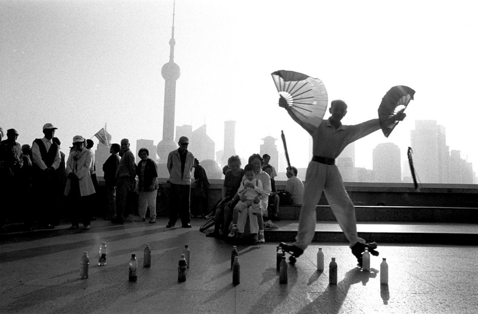 A retired circus performer executes early morning roller skating tricks on the Huang Pu River in Shanghai. (Ryan Pyle)