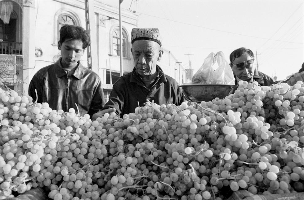 Men shop for grapes at a street market in Kashgar, Xinjiang. (Ryan Pyle)