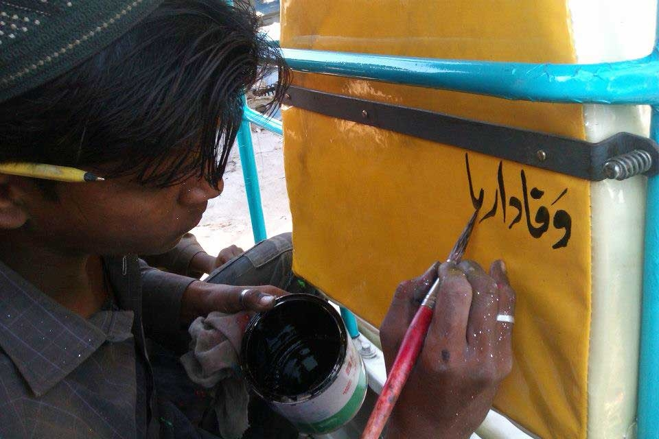A young artist paints a verse on the back of one of the rickshaws. (Pakistan Youth Alliance)