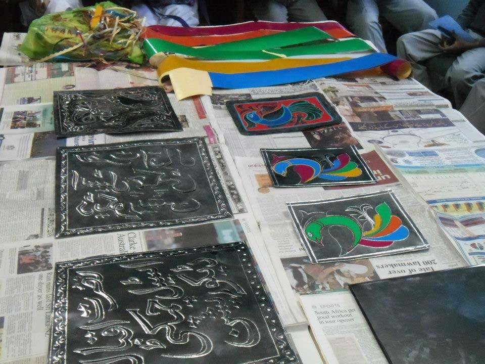 Etched metal plates laid out to be finished in brightly colored reflective stickers. (Pakistan Youth Alliance)