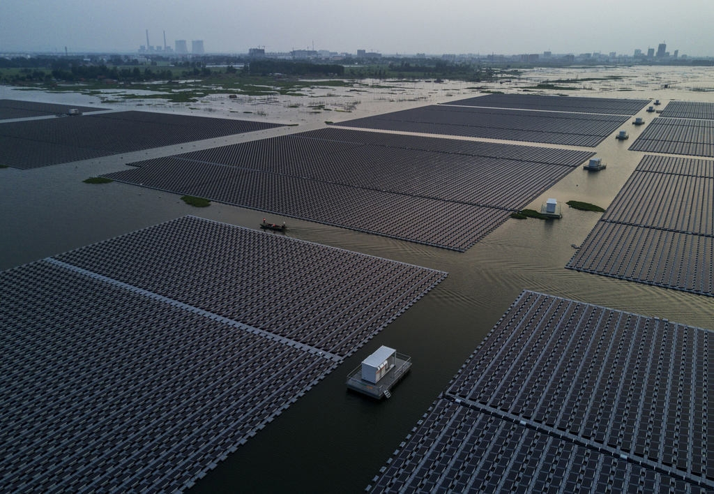 Chinese workers ride in a boat through a large floating solar farm project under construction by the Sungrow Power Supply Company on a lake caused by a collapsed and flooded coal mine on June 13, 2017 in Huainan, Anhui province, China. The floating solar field is billed as the largest in the world. (Kevin Frayer/Getty Images)
