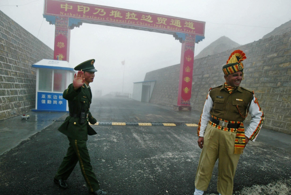 On July 10, 2008 a Chinese soldier and an Indian soldier stand guard at the Chinese side of the ancient Nathu La border crossing between India and China. (Diptendu Dutta/AFP/Getty Images)