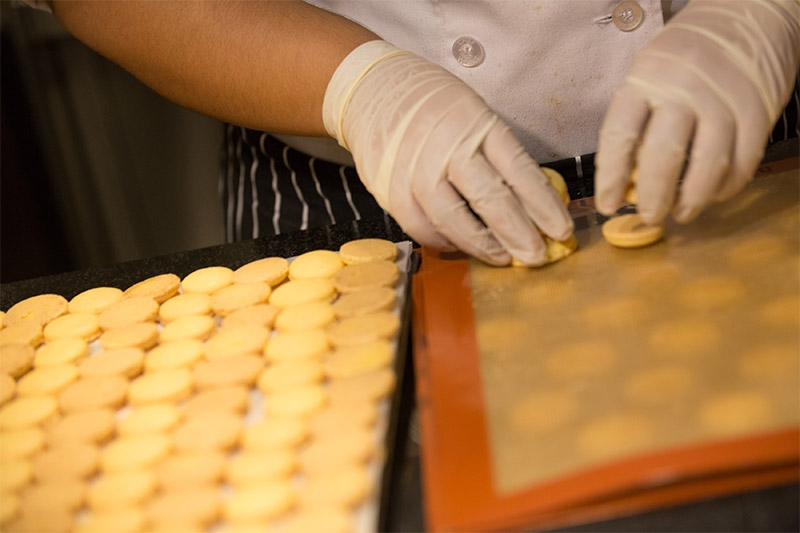 A student cooks macaron cookies.