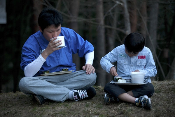 Tsunami survivors Shota Endo (L) and Kei Endo eat relief food outside an evacuation center suffering from power cuts in Shichigahama town, Miyagi prefecture on April 8, 2011. (Yasuyoshi Chiba/AFP/Getty Images)