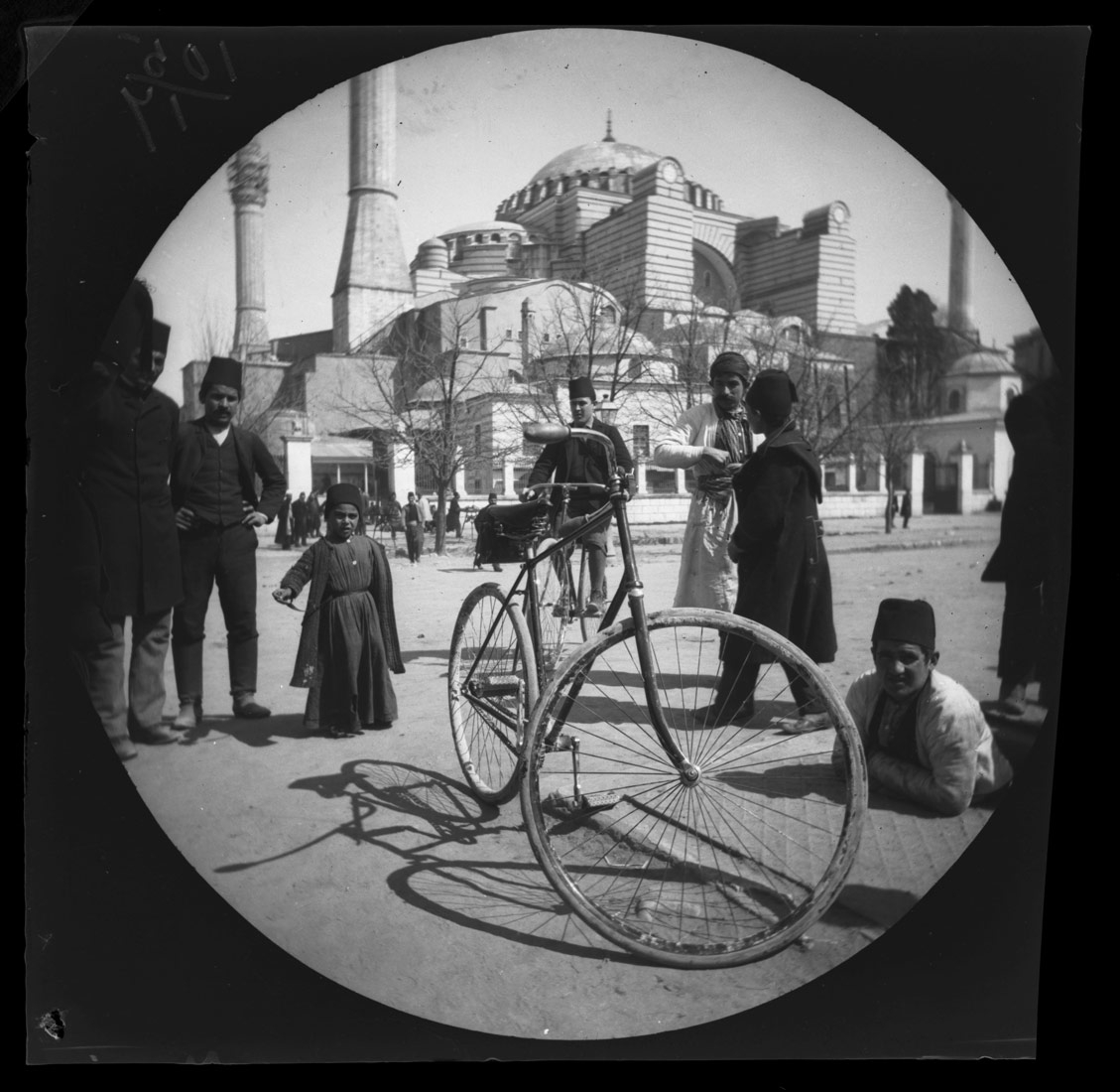 William Sachtleben's Humber bicycle at rest in Constantinople draws a crowd of spectators.  Background: Hagia Sophia and Thomas Allen on his bicycle.  March 21, 1891. Collection of the UCLA Library Special Collections