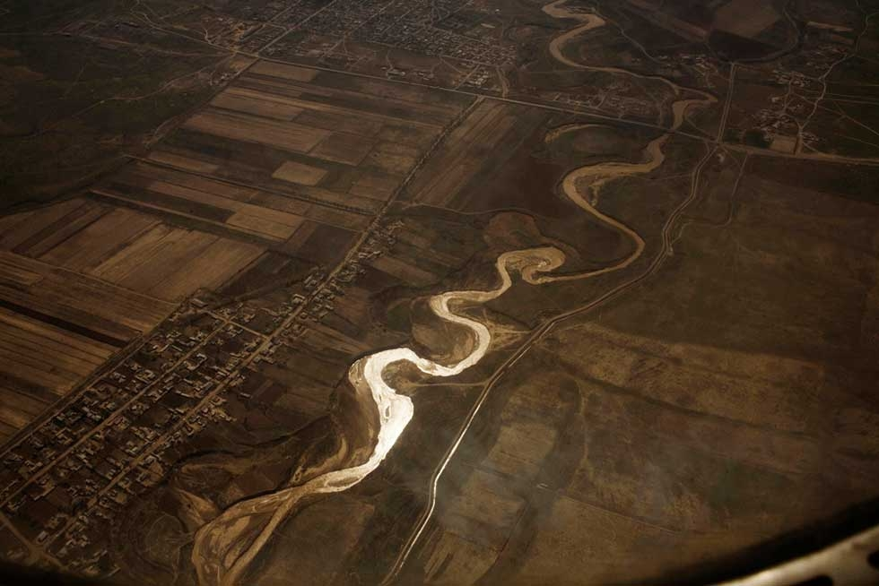 "Overhead view of the Syr Darya river in Uzbekistan, with an irrigation canal on the right. From ""Two Rivers."" (Carolyn Drake)"