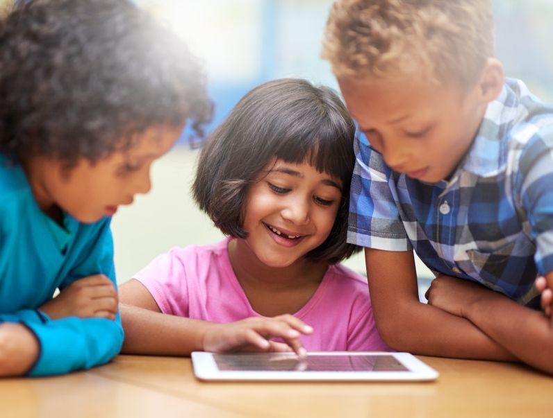 Children look at a tablet together.