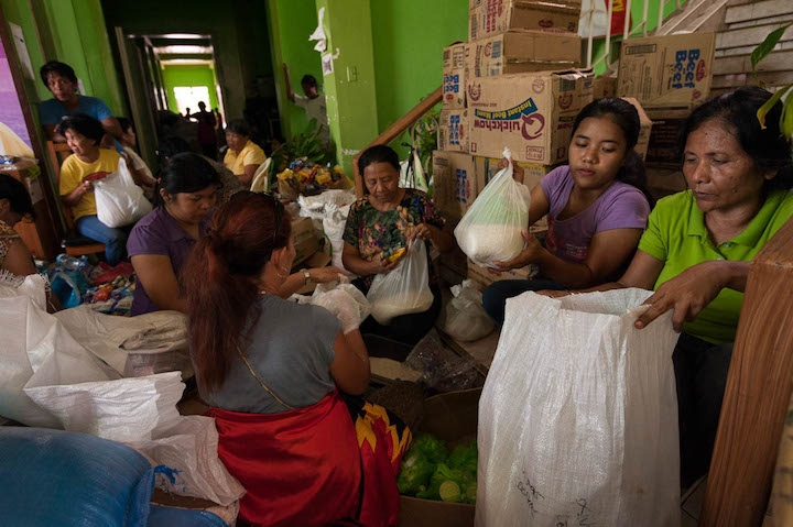 Staff from the local government packs relief goods at the municipality of Medellin, Bogo after Typhoon Yolanda.