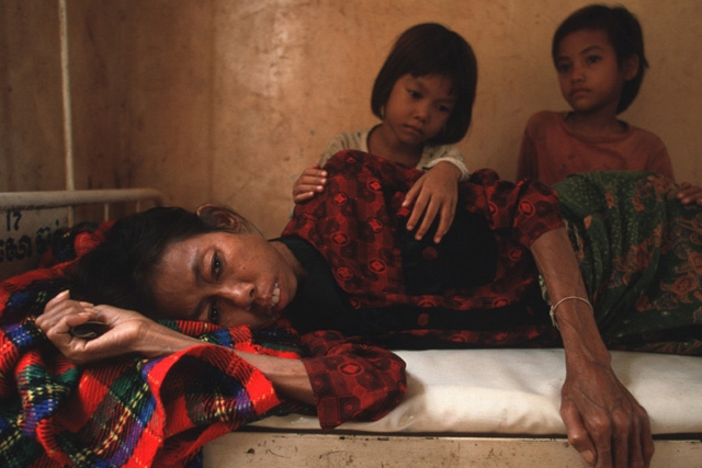 Two daughters look at their mother who is dying from HIV/AIDS in Cambodia. (Photo by Masaru Goto / World Bank)