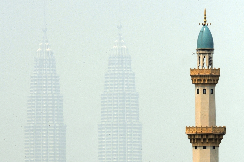 Malaysia's landmark Petronas Twin Towers are enveloped by haze behind the minerat of a mosque in Kuala Lumpur on June 12, 2009. (Saeed Khan/AFP/Getty Images)
