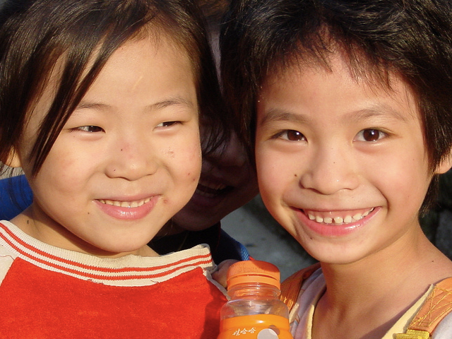 Two children smiling. (Planet Love/flickr)