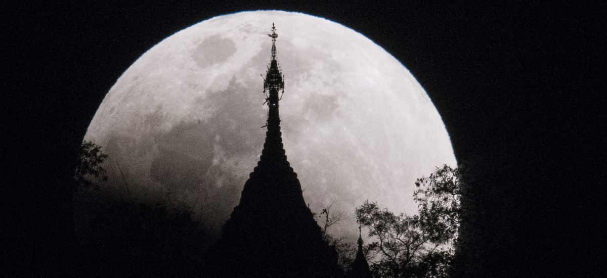 Moon rises over a pagoda in Kumal, Myanmar