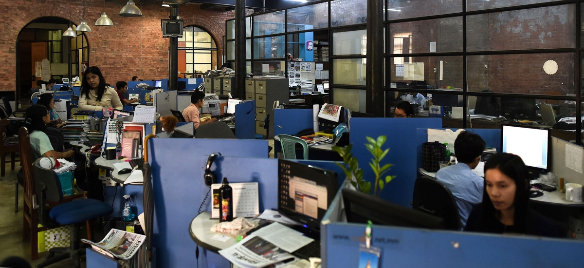 Journalists work in the newsroom of a newspaper in Yangon, Myanmar.