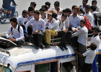Pakistani students sit on top of an overloaded mini bus.