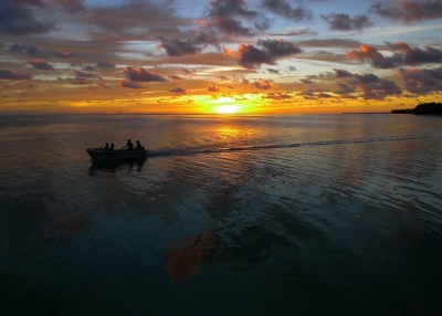 A speed boat zips away from the setting sun in Tabiteuea North, Kiribati on May 25, 2012. (Steve Bolton/Flickr)