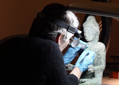 "Art conservator Leslie Gat at work removing bronze disease from a sculpture featured in Asia Society Museum's exhibition ""Buddhist Art of Myanmar."""