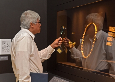 A museum visitor uses a magnifying glass to inspect an item curated in the 'Philippine Gold' exhibition.