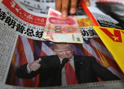 A vendor picks up a 100 yuan note above a newspaper featuring a photo of U.S. president-elect Donald Trump, at a news stand in Beijing on November 10, 2016. (Greg Baker/AFP/Getty Images)