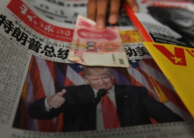A vendor picks up a 100 yuan note above a newspaper featuring a photo of U.S. President Donald Trump at a news stand in Beijing on November 10, 2016. (Greg Baker/AFP/Getty Images)