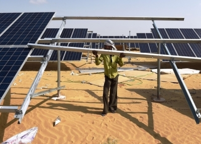 In this photograph taken on August 23, 2015, an Indian engineer fixes a solar panel into position at the under construction Roha Dyechem solar plant at Bhadla some 225 kms north of Jodhpur in the western Indian state of Rajasthan. (Money Sharma/Getty Images)