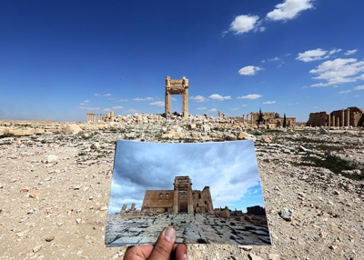 On March 31, 2016, a photographer holds his picture of the Temple of Bel taken on March 14, 2014 in front of the remains of the historic temple after it was destroyed by Islamic State group jihadists in September 2015 in the ancient Syrian city of Palmyra. (Joseph Eid/AFP/Getty Images)