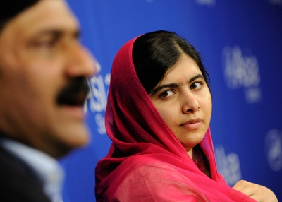 Malala Yousafzai listens as her father, Ziauddin Yousafzai, addresses attendees at Asia Society In New York