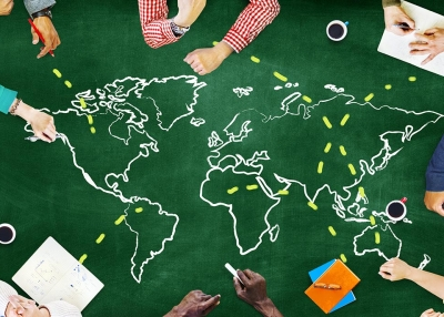 People collaborate around a map of the world.