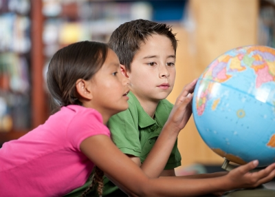 Two students look at a globe