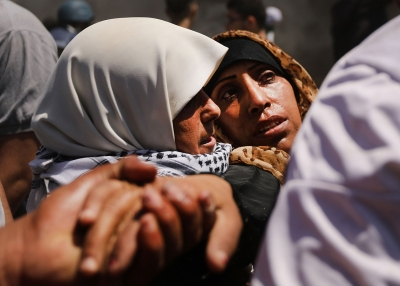 A wounded Palestinian women is carried from the border fence with Israel