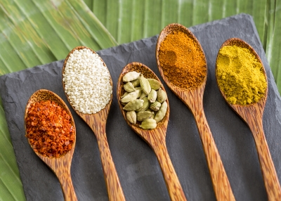 indian spices on wooden spoons with a backdrop of leaves and slate