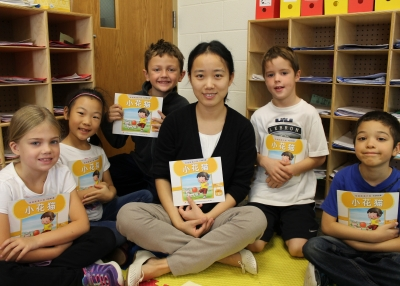 Forest Hills Public Schools elementary students read a book with their teacher.