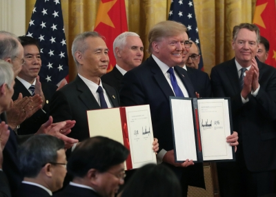 Liu He and Donald Trump hold up signed agreements of phase one of the U.S.-China trade deal