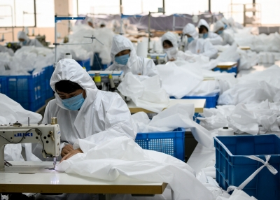 Workers, sewing, at a factory making hazardous material suits to be used in the COVID-19 pandemic.