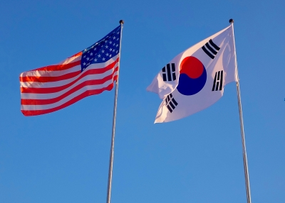 U.S. and South Korean flags against a blue sky
