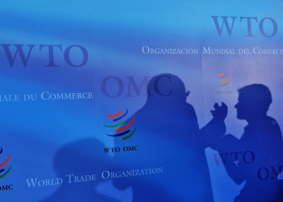 Two silhouettes on a blue backdrop at the World Trade Organization