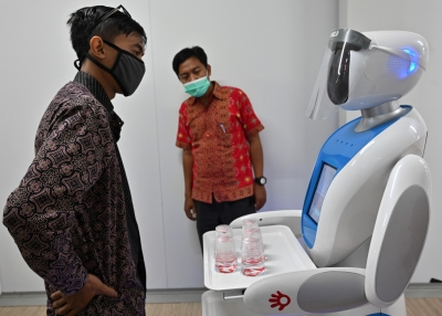 Indonesian technician with a robot during a simulation on assisting medical teams in handling COVID-19 coronavirus patients in Jakarta.