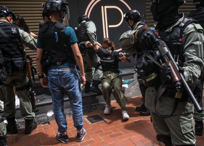 Riot police detaining a woman as they clear protesters taking part in a rally against a new national security law in Hong Kong.