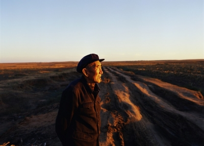 An elderly man looks towards the sunset