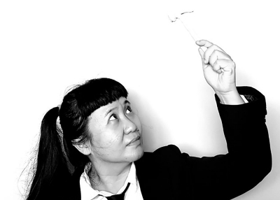 A black-and-white portrait of anGie seah, who is dressed in a black blazer, white collared shirt, and black tie. Her long hair is in pigtails. She gazes upwards towards her raised hand, which is holding a miniature hammer.
