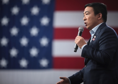 Andrew Yang delivering a speech in front of the American flag