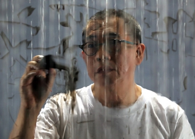 """Writing in the Rain."" FX Harsono, 2011. Single-channel video with sound Duration: 6 minutes, 2 seconds.  Image courtesy of the artist and Tyler Rollins Fine Art."
