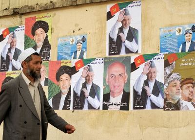 A man walks past posters of Aghan presidential candidates in Kabul on June 16, 2009. (Shah Marai/AFP/Getty Images)