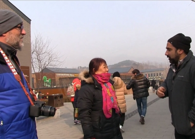 Greg Matza talks to a woman about visiting an older part of the Great Wall.