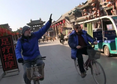 Howie Southworth (left) and Greg Matza ride through Ping Yao.